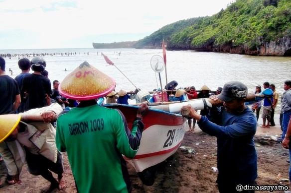 Nelayan gotong royong melabuhkan kapal